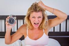 Mulher que guarda o despertador foto de stock royalty free