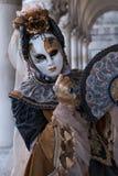 Mulher que guarda o fã e que veste o traje do máscara e o ornamentado do ouro e o preto sob os arcos no palácio dos doges durante Imagens de Stock