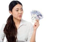 Mulher que guarda o fã da moeda Imagens de Stock