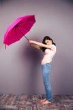 Mulher que guarda o guarda-chuva sobre a parede cinzenta fotografia de stock