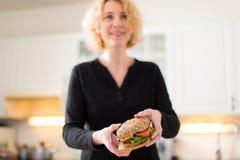 Mulher que guarda o hamburguer imagem de stock