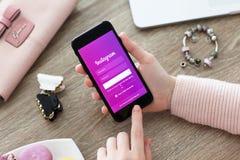 Mulher que guarda o iPhone 7 Jet Black Onyx com serviço Instagram Foto de Stock