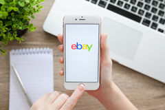 Mulher que guarda o iPhone 6S Rose Gold com Ebay na tela foto de stock