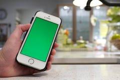 Mulher que guarda o iphone verde da tela Fotografia de Stock