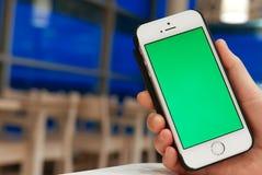Mulher que guarda o iphone verde da tela Imagens de Stock