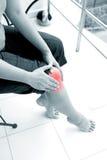 Mulher que guarda o joelho direito com ambas as mãos ao sentar-se para baixo para mostrar a dor no joelho Fotos de Stock Royalty Free