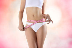 A mulher que guarda o medidor cor-de-rosa com mãos aproxima a cintura, em um rosa fotografia de stock royalty free