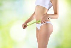 A mulher que guarda o medidor verde com mãos aproxima a cintura, em um verde fotografia de stock