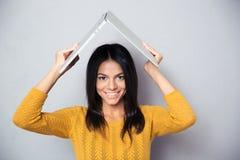 A mulher que guarda o portátil acima de sua cabeça gosta de um telhado Fotos de Stock Royalty Free