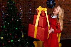 Mulher que guarda o presente vermelho grande do Natal fotografia de stock royalty free