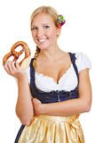 Mulher que guarda o pretzel no dirndl Fotos de Stock