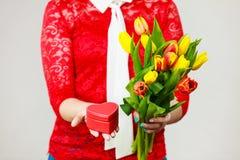 Mulher que guarda o ramalhete amarelo e alaranjado das tulipas imagens de stock