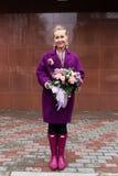 Mulher que guarda o ramalhete bonito das flores Fotografia de Stock