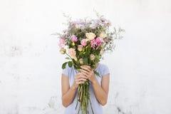 Mulher que guarda o ramalhete das flores Fotos de Stock Royalty Free