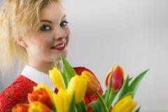 Mulher que guarda o ramalhete de flores das tulipas foto de stock
