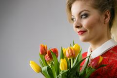 Mulher que guarda o ramalhete de flores das tulipas imagens de stock