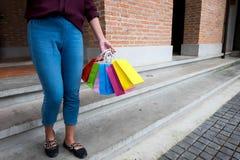 Mulher que guarda o saco de compras ao andar na rua do vintage, conceito de compra foto de stock royalty free