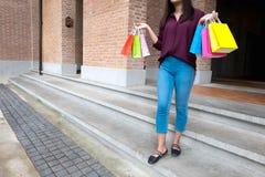 Mulher que guarda o saco de compras ao andar na rua do vintage, conceito de compra fotografia de stock royalty free