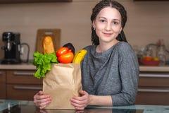 Mulher que guarda o saco de papel completo com os produtos no fundo da cozinha Alimento biológico fresco para uma dieta equilibr fotos de stock royalty free