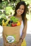 Mulher que guarda o saco de papel da compra com os vegetais e frutos orgânicos ou bio. Imagem de Stock