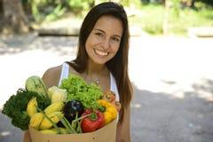 Mulher que guarda o saco de papel da compra com os vegetais e frutos orgânicos ou bio. Imagens de Stock