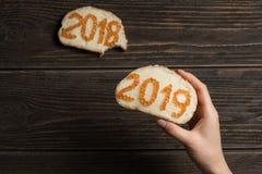 Mulher que guarda o sanduíche vermelho do caviar 2019 com o sanduíche 2018 mordido no fundo foto de stock