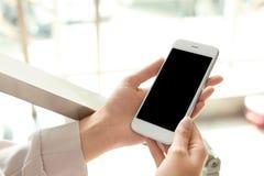 Mulher que guarda o smartphone com tela vazia fotos de stock royalty free