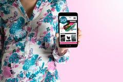 Mulher que guarda o smartphone Web site em linha de compra Fotografia de Stock Royalty Free