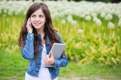Mulher que guarda o tablet pc e que fala no telefone Imagens de Stock Royalty Free