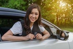 Mulher que guarda o telecontrole chave esperto com um carro foto de stock royalty free