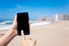 Mulher que guarda o telefone celular/telefone celular em uma praia no verão imagens de stock royalty free