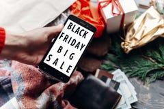 Mulher que guarda o telefone com oferta especial dis da venda grande preta de sexta-feira Fotos de Stock Royalty Free