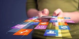Mulher que guarda o telefone esperto com ícones coloridos da aplicação Fotografia de Stock