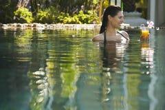 Mulher que guarda o vidro de Juice In Pool alaranjado fotografia de stock royalty free