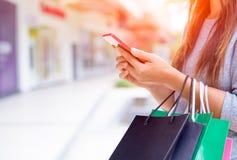 Mulher que guarda os sacos de compras que fazem a compra em linha em seu móbil fotografia de stock