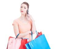 Mulher que guarda os sacos de compras que têm um telefonema Fotos de Stock Royalty Free