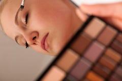 Mulher que guarda a paleta das sombras com espelho e que faz o makeu Foto de Stock Royalty Free