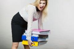 Mulher que guarda pastas coloridas pesadas com originais Foto de Stock