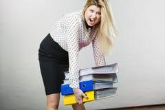 Mulher que guarda pastas coloridas pesadas com originais Imagem de Stock