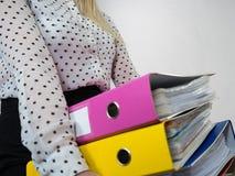 Mulher que guarda pastas coloridas pesadas com originais Foto de Stock Royalty Free