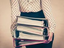 Mulher que guarda pastas coloridas pesadas com originais Fotografia de Stock Royalty Free