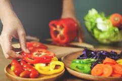 Mulher que guarda pimentas de sino vermelhas Cozinhando o alimento do vegetariano sagacidade saudável Foto de Stock Royalty Free