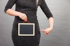 Mulher que guarda a placa preta vazia no gancho fotografia de stock