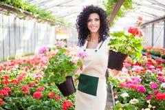 Mulher que guarda potenciômetros de flor fotografia de stock royalty free