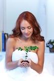 Mulher que guarda pouca planta em suas mãos Imagem de Stock Royalty Free