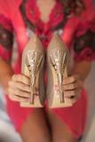 Mulher que guarda sapatas novas do nude do salto alto nas mãos Fotografia de Stock Royalty Free