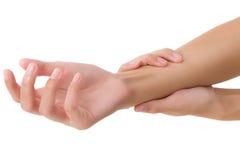 Mulher que guarda seu pulso saudável bonito e que faz massagens na área da dor Fotos de Stock