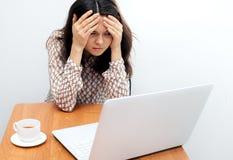 Mulher que guarda sua cabeça no escritório perto do portátil Imagens de Stock