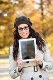Mulher que guarda a tabuleta digital no outono fotografia de stock royalty free