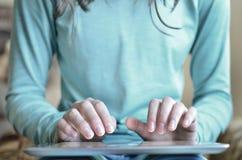 Mulher que guarda a tabuleta e que usa o dedo Imagens de Stock